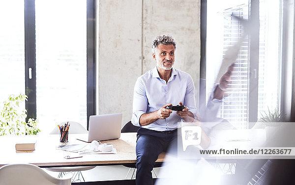 Lächelnder  reifer Geschäftsmann  der im Büro auf dem Schreibtisch sitzt und den Controller benutzt.