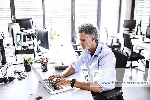 Reife Geschäftsleute sitzen am Schreibtisch im Büro mit Laptop