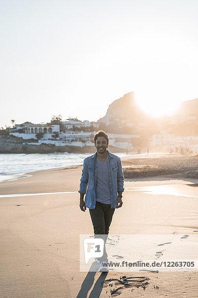 Glücklicher junger Mann  der bei Sonnenuntergang am Strand spazieren geht.