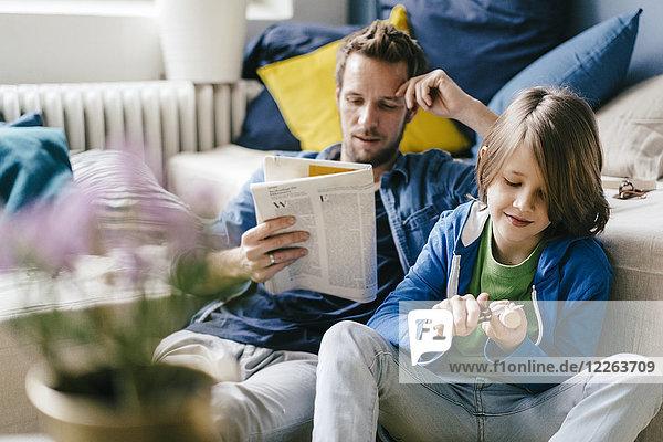 Vater liest Zeitung  während der Sohn zu Hause schnitzt.