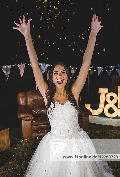 Cheerful bride raising her arms while confetti falling over her on a night party outdoors