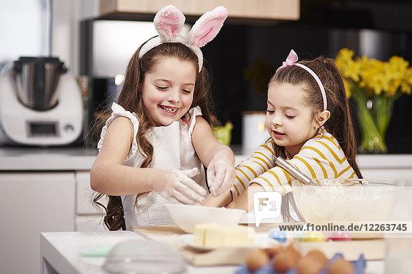 Zwei Schwestern beim gemeinsamen Ostergebäckbacken in der Küche