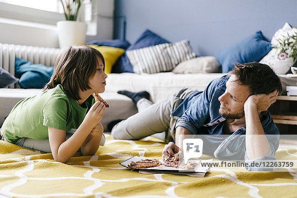 Vater und Sohn essen Pizza auf dem Boden zu Hause