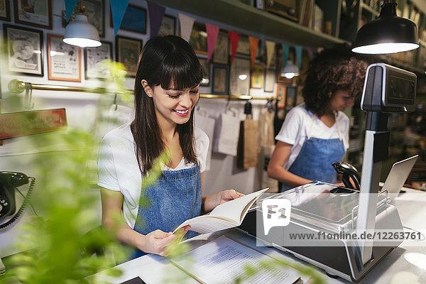 Lächelnde Frau an der Theke in einem Laden  die in ein Notizbuch schaut.
