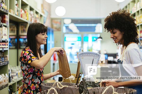 Lächelnder Kunde und Verkäufer am Tresen eines Ladens