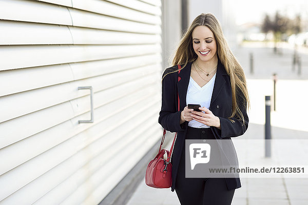Portrait of content businesswoman using cell phone
