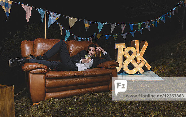 Portrait of man in suit posing on sofa on a night field party