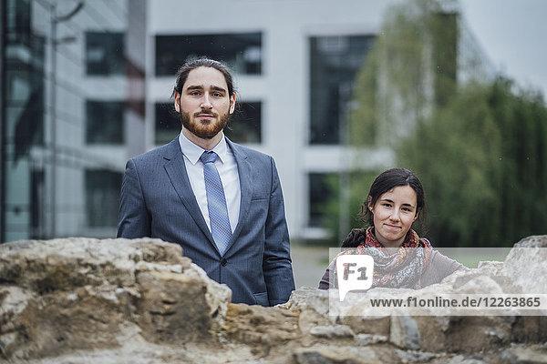 Porträt eines Geschäftsmannes und einer Frau hinter einer Wand vor dem Bürogebäude