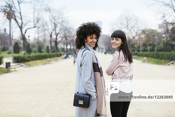 Spain  Barcelona  portrait of two smiling women in city park turning round