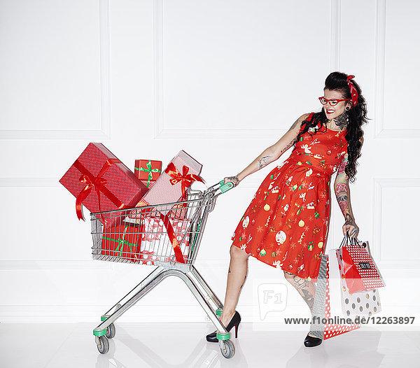 Tätowierte Frau mit Einkaufstaschen und Einkaufswagen voller Geschenke