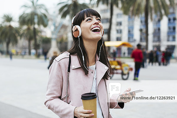 Spain  Barcelona  laughing woman with coffee  cell phone and headphones in the city