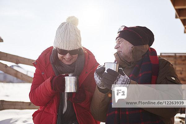 Fröhliches reifes Paar mit heißen Getränken auf der Almhütte im Winter