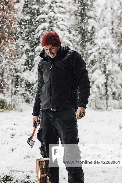 Kanada  Mann hackt Holz bei Schneefall
