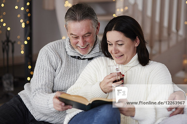 Glückliches reifes Paar beim Lesen eines Buches im Wohnzimmer