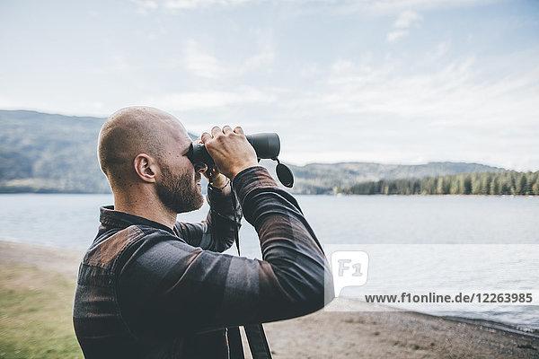 Kanada  British Columbia  Mann schaut durchs Fernglas am Cultus Lake