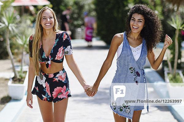 Porträt von zwei glücklichen jungen Frauen  die im Sommer Händchen halten