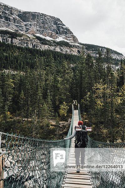 Kanada  British Columbia  Mount Robson Provincial Park  zwei Männer auf Drehbrücke am Berg Lake Trail