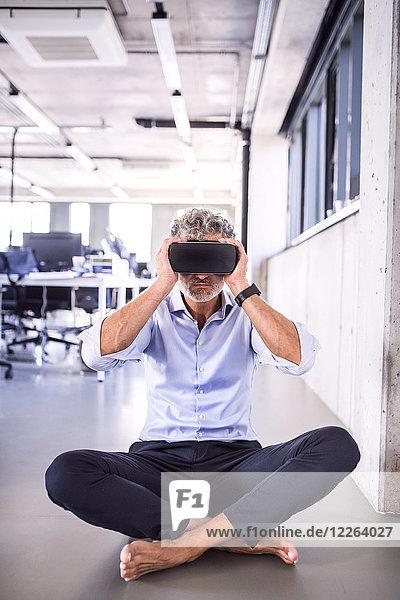 Barfuss reifer Geschäftsmann mit VR-Brille auf dem Boden im Büro sitzend