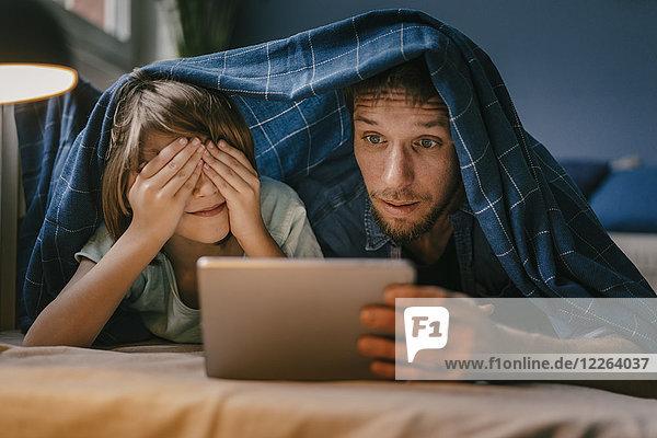 Aufgeregter Vater und Sohn beim Betrachten eines Films auf Tablett unter der Decke