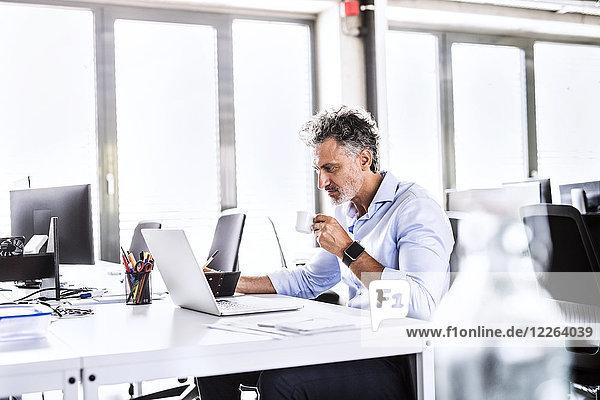 Erwachsener Geschäftsmann am Schreibtisch im Büro mit Laptop und Kaffeetrinken