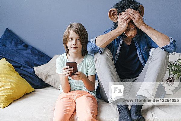 Vater mit Affenmaske sitzt neben dem Sohn und benutzt das Smartphone zu Hause.
