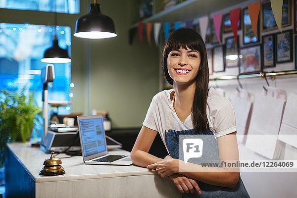 Portrait einer glücklichen Frau mit Laptop im Laden