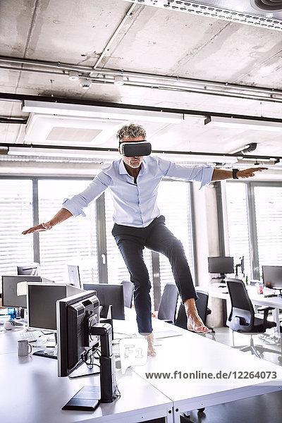 Barfuss reifer Geschäftsmann auf Schreibtisch im Büro mit VR-Brille