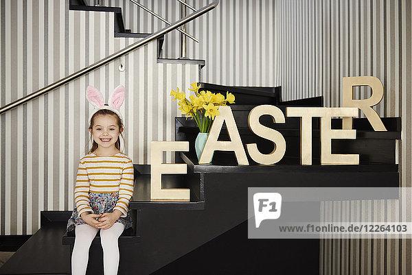 Porträt eines lächelnden Mädchens mit Hasenohren auf einer Treppe neben dem Wort'Ostern'.