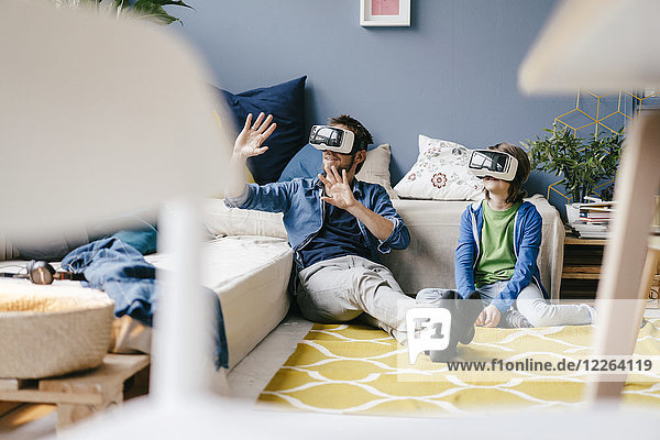 Vater und Sohn mit VR-Brille zu Hause auf dem Boden sitzend