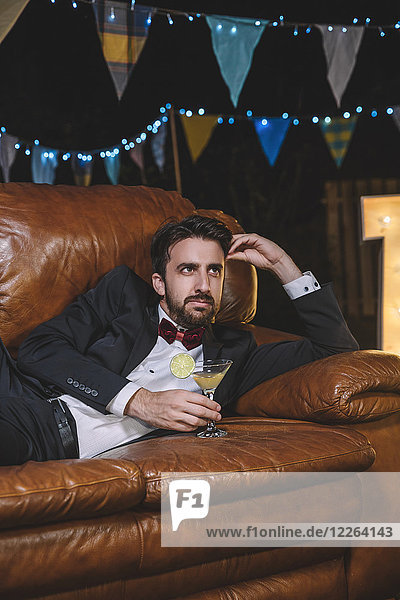 Pensive man in suit lying on sofa on a night party oitdoors