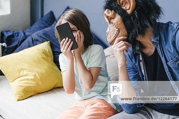 Vater trägt eine Affenmaske und sieht den Sohn mit dem Smartphone zu Hause an.