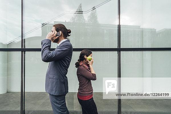 Geschäftsmann im Gespräch mit einer Frau  die einen Apfel am Ohr hält.