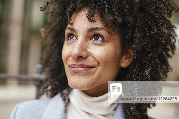 Porträt einer lächelnden Frau  die nach oben schaut