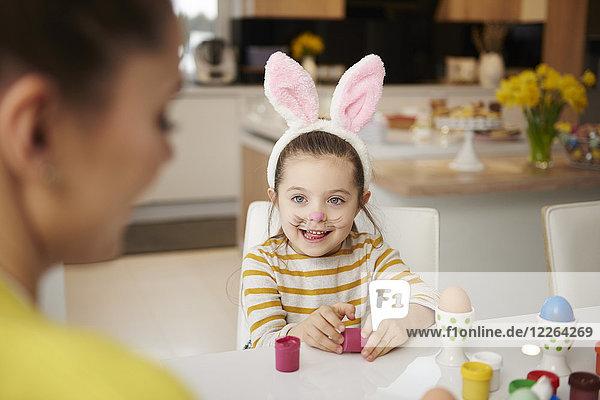Mädchen mit Hasenohren und Mutter am Tisch sitzend mit Ostereiern