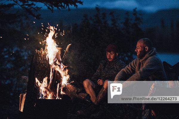 Kanada  British Columbia  zwei Männer sitzen nachts am Lagerfeuer am Boya Lake.