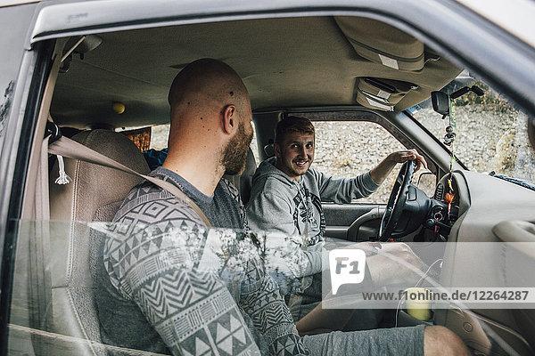 Zwei lächelnde junge Männer im Auto auf einem Roadtrip