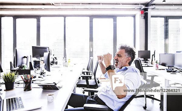 Glücklicher reifer Geschäftsmann  der am Schreibtisch im Büro jubelt.