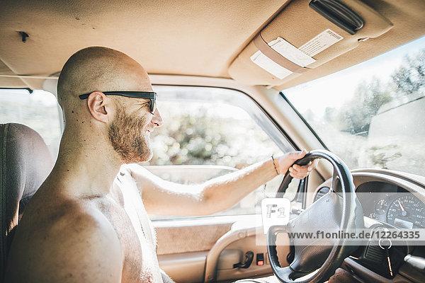 Barechested glücklich junger Mann mit Sonnenbrille und Bart auf einem Roadtrip