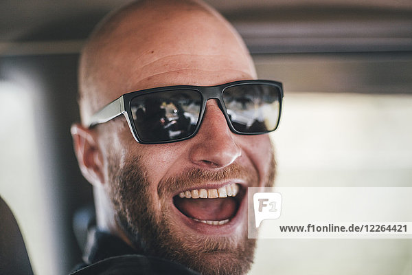 Porträt eines glücklichen jungen Mannes mit Sonnenbrille und Bart auf einem Roadtrip