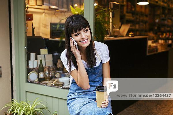 Lächelnde Frau sitzt an der Eingangstür eines Ladens und redet mit dem Handy.