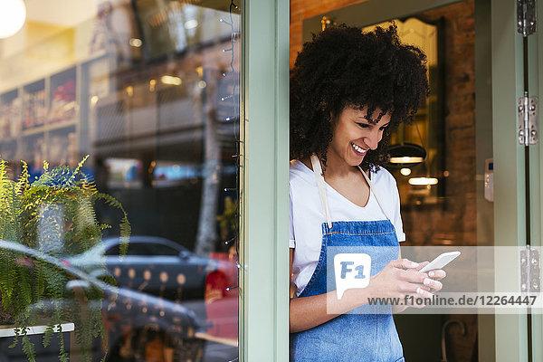 Lächelnde Frau mit Handy in der Eingangstür eines Ladens