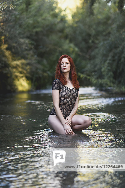 Portrait of redheaded young woman wearing transparent black bodysuit crouching in water
