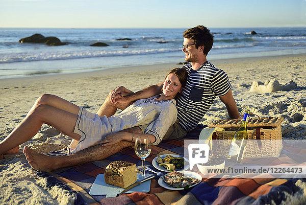 Glückliches Paar beim Picknick am Strand