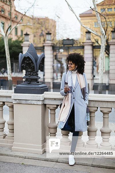 Spanien  Barcelona  lächelnde Frau mit Handy und Kopfhörer in der Stadt schaut weg