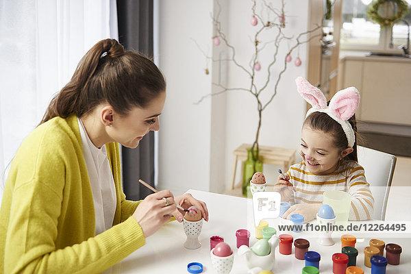 Glückliche Mutter und Tochter mit Hasenohren sitzen am Tisch und malen Ostereier.