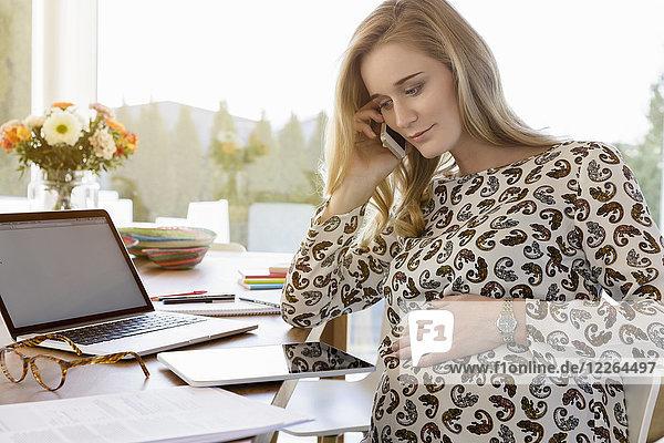 Schwangere Frau am Schreibtisch am Telefon
