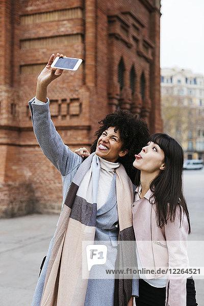 Spanien  Barcelona  zwei verspielte Frauen  die einen Selfie an einem Tor nehmen.