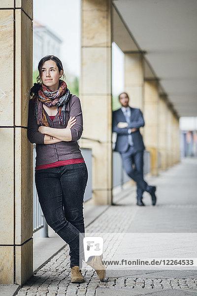 Frau steht an einer Arkade mit einem Geschäftsmann hinter ihr.