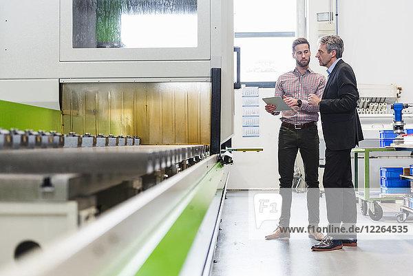 Geschäftsleute mit Tablette bei der Besprechung in der Produktionshalle