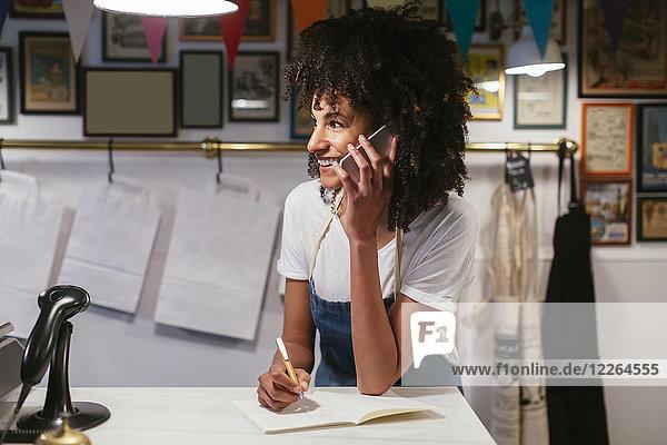 Lächelnde Frau am Telefon in einem Laden  die sich Notizen macht.